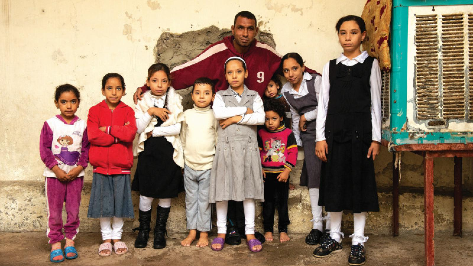 Ahmad and the nine children, he provides for, in front of their house which is now in a better condition thanks to Danish support. Photo: Philip Hartzner