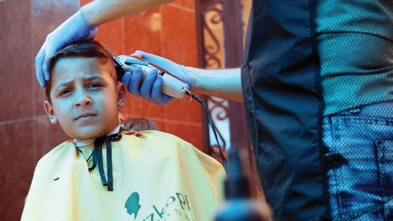 Khaled used to be afraid of haircuts, but at Mission East's community centre in Mosul it is different. Photo: Binar Mohammed