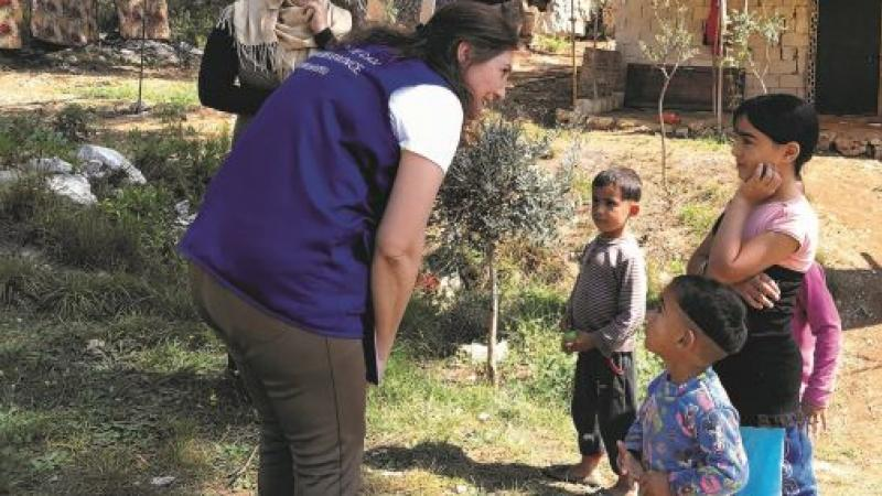 A Mission East staff member talking to refugee children in a refugee camp i Lebanon