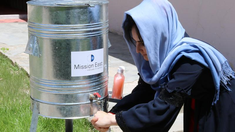 Afghan girl washing her hands at a clean water dispenser provided by Mission East